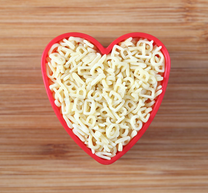 I love alphabet pasta. Raw alphabet soup pasta in a heart bowl. Close-up royalty free stock image