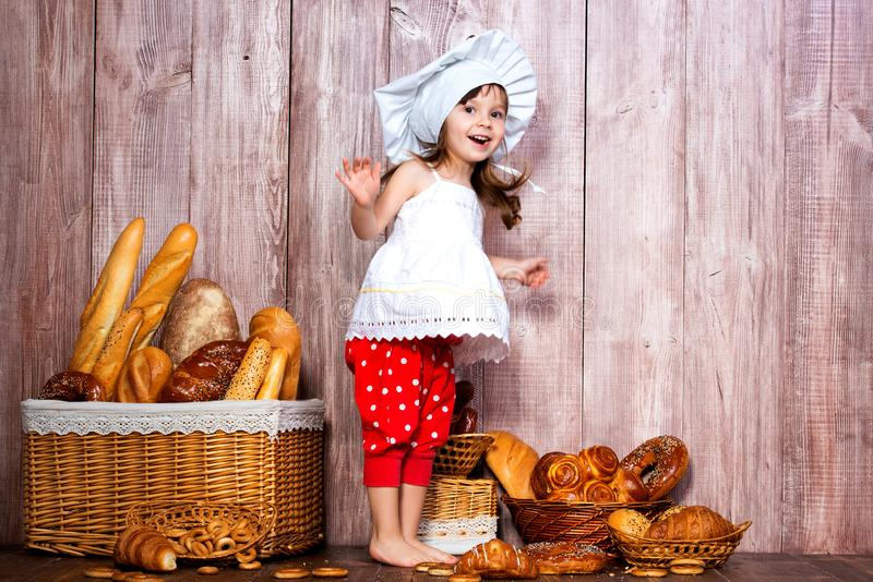 I love buns. Little smiling girl in a cooking cap jumping for joy and delight near a wicker basket with bread rolls and bakery royalty free stock photography