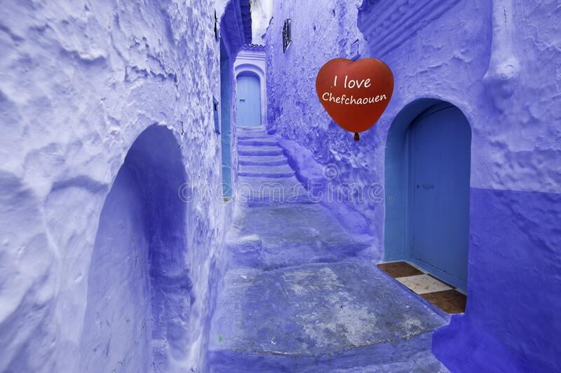`i love Chefchaouen` baloon in the blue town. Red heart-shaped baloon in an alley of the blue town chefchaouen with its blue painted walls and doors stock photo