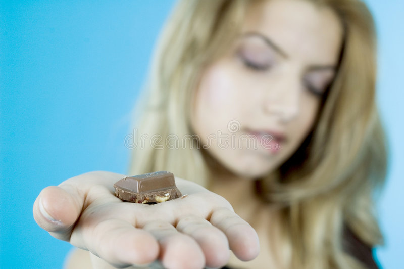 I Love Chocolate 3. A chunk of chocolate in the open palm of a woman, whose face is blurred in the background. Taken in studio with a blue background stock photo