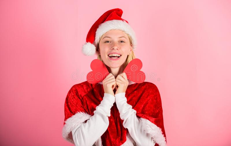 I love christmas. Girl happy wear santa costume celebrate christmas pink background. Merry christmas and happy new year. Woman hold heart symbol of love. Bring stock image