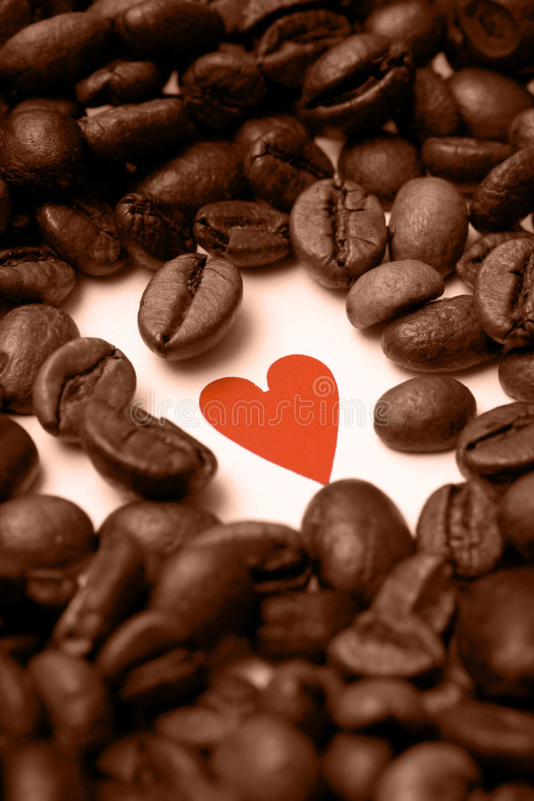 I love coffee. A shape of a heart discovered under a coffee beans pile stock images