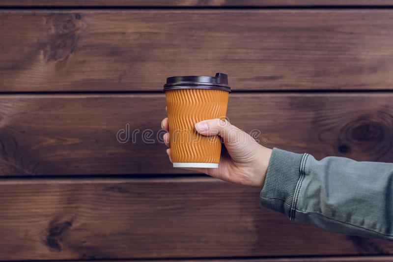 I love coffee! Person`s hand holding cup of coffee in front of brown wooden background takeaway take away takeout break rest rela royalty free stock image
