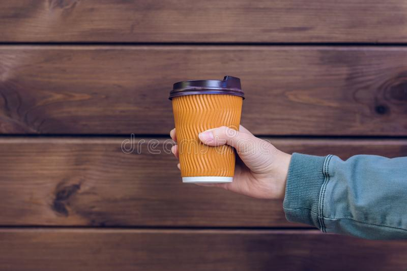 I love coffee! Person`s hand holding cup of coffee in front of brown wooden background takeaway takeaway takeout food drink beve. Rage morning paper cup mug hand stock images