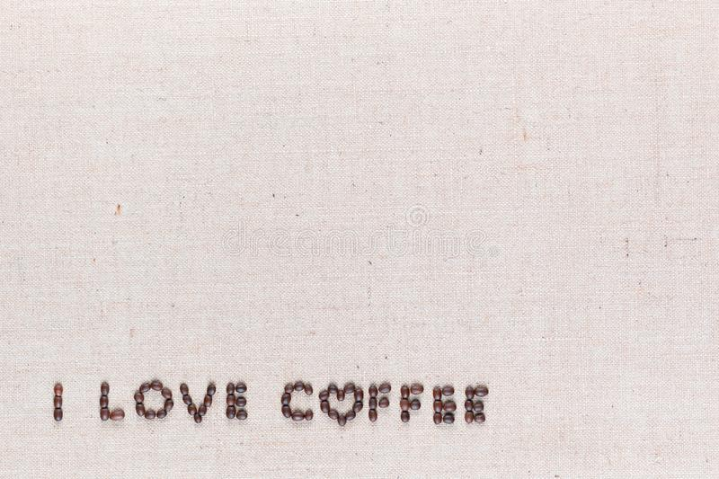 I love coffee sign from coffee beans on linen canvas, arranged bottom left. `I love coffee` words made from roasted coffee beans on linen texture, shot from royalty free stock image