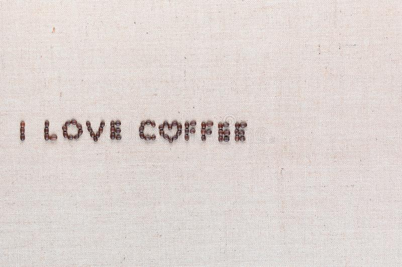I love coffee sign from coffee beans on linen canvas, arranged middle left. `I love coffee` words made from roasted coffee beans on linen texture, shot from stock image