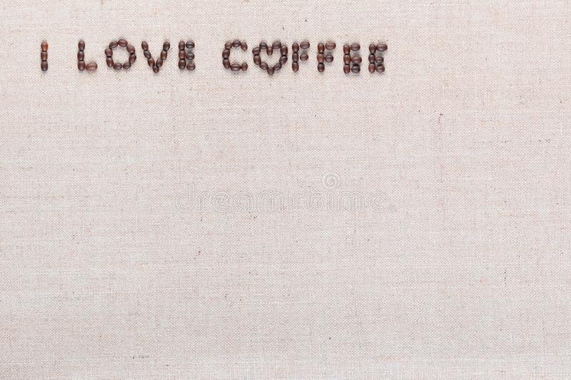 I love coffee sign from coffee beans on linen canvas, arranged top left. `I love coffee` words made from roasted coffee beans on linen texture, shot from above stock image