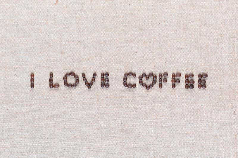 I love coffee sign from coffee beans on linen canvas, shot close up. `I love coffee` words made from roasted coffee beans on linen texture, shot from above royalty free stock photo
