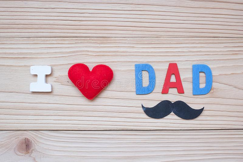 I Love DAD text with red heart shape and mustache on wooden background. Happy Father`s Day and International Men`s Day concepts stock photo