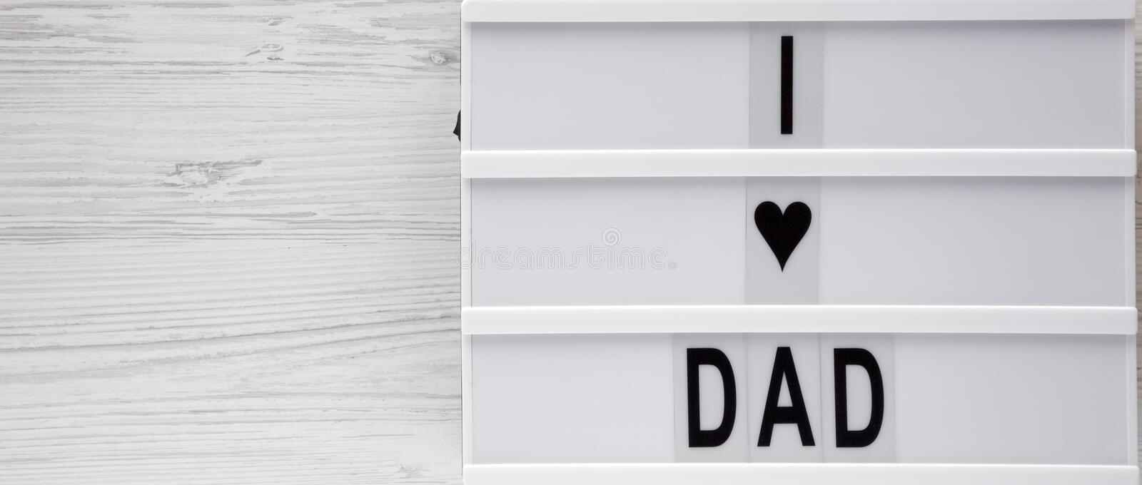 `I love dad` words on a light box over white wooden background, top view. Overhead, from above, flat lay. Copy space.  royalty free illustration