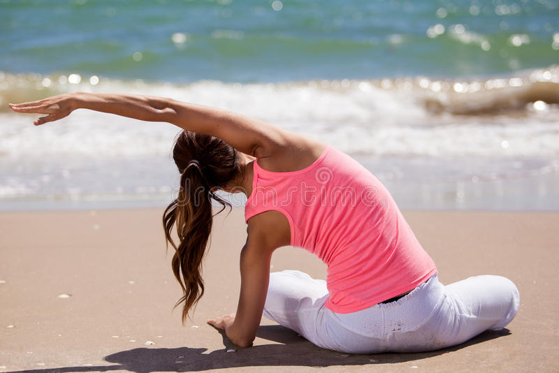 I love doing yoga at the beach. Young woman doing some stretching exercises for her yoga practice at the beach stock photo