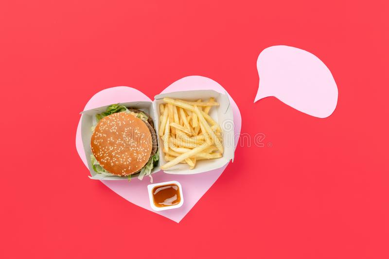 I love fast food. French fries in the form of heart isolated on red background. I love fast food. French fries, burger in the form of heart isolated on red royalty free stock photos