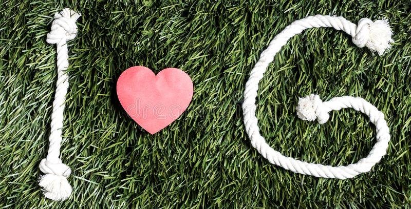 I love G transcription made from ropes on grass background. I love G transcription made from ropes on grass background royalty free stock photography