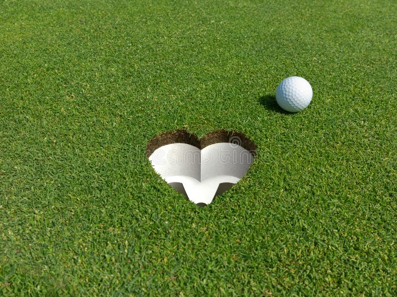 I love golf golfball and hole with the shape of e heart royalty free stock image