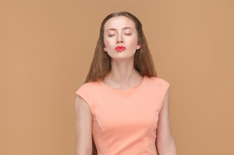 I love and kiss you. Portrait of emotional cute, beautiful woman with makeup and long hair in pink dress. indoor, studio shot, isolated on light brown or beige royalty free stock photography