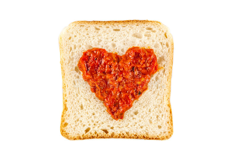 I love lutenica concept. Traditional Bulgarian relish spead as a heart shape on a white bread royalty free stock photo