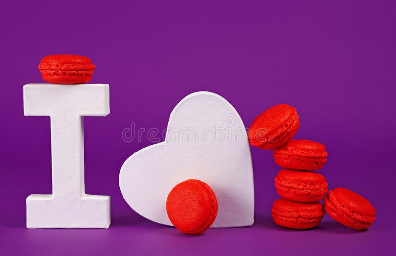 I love macaroons. Strawberry macaroons on a purple background with the letter 'I' and a white heart to mean: 'I love macaroons stock images