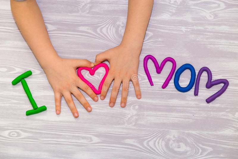 I love mom text from plasticine with kid hands on white wooden background. Happy mothers day. kids handmade craft present. I love mom text from plasticine with royalty free stock photography