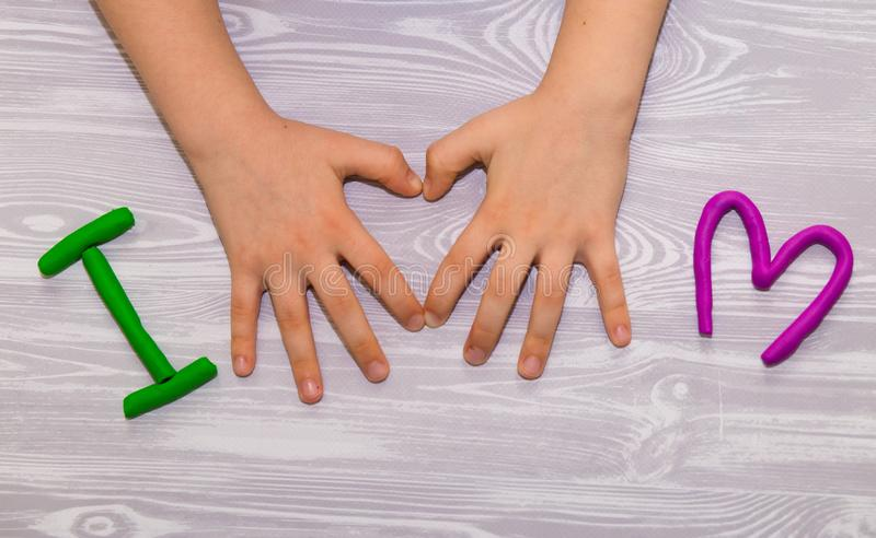 I love mom text from plasticine with kid hands on white wooden background. Happy mothers day. kids handmade craft present. I love mom text from plasticine with stock photo