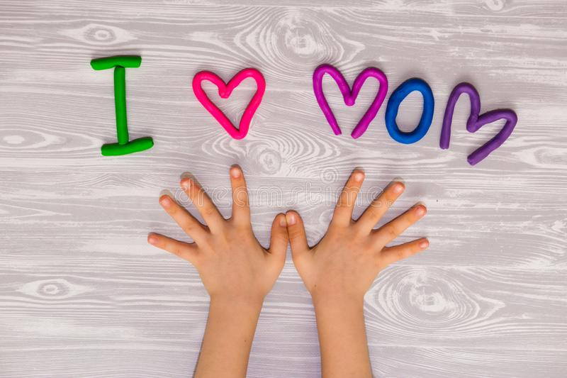 I love mom text from plasticine with kid hands on white wooden background. Happy mothers day. kids handmade craft present. I love mom text from plasticine with stock photography