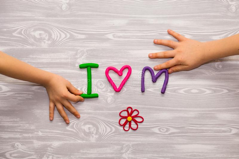 I love mom text from plasticine with kid hands on white wooden background. Happy mothers day. kids handmade craft present. I love mom text from plasticine with stock images