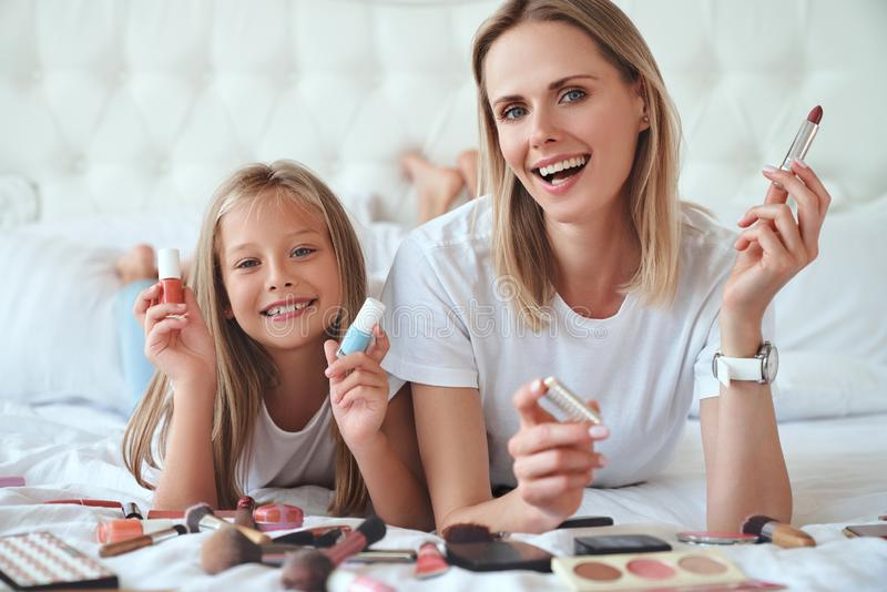 I love my mom. Happy Mothers Day. Beautiful mom with her little cute daughter are having fun at home. Doing makeup and smiling. royalty free stock photos