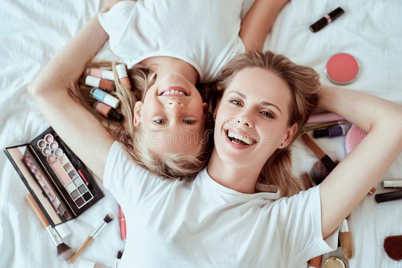 I love my mom. Happy Mothers Day. Top view of beautiful mom with her little cute daughter are having fun at home. Doing makeup and. Smiling while lying on bed royalty free stock photos