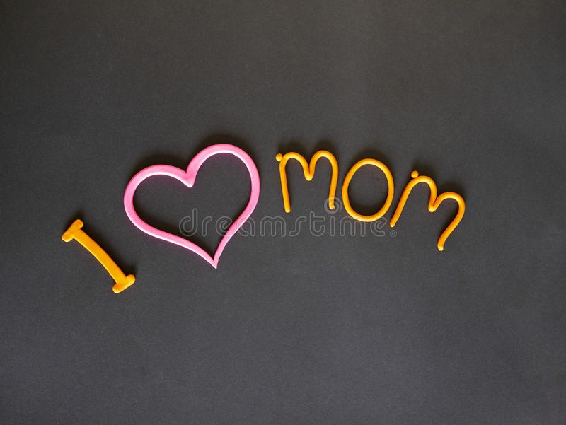 I love my mother the inscription of yellow plasticine with a pink heart. On grey background stock photo