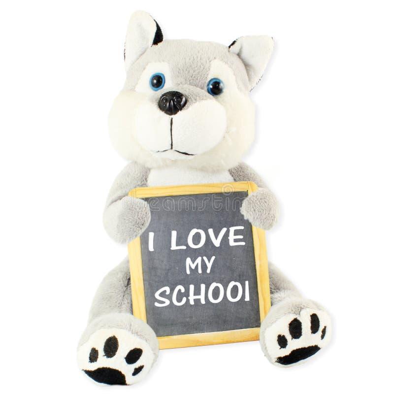 I love my school written with chalk on the school blackboard in hand of teddy bear royalty free stock photos