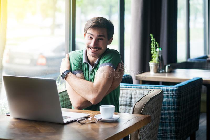 I love myself! Young happy satisfied businessman in green t-shirt sitting, hugging himself and looking at camera with toothy smile stock photo