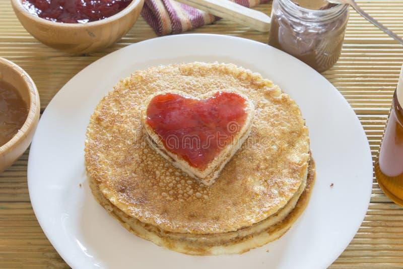 I love pancakes. Heart shaped pancake with strawberry jam. On stack of pancakesHeart shaped pancake with strawberry jam on stack of pancakes royalty free stock image