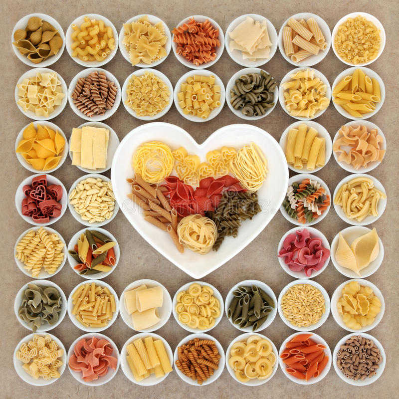 I Love Pasta. Dried pasta spaghetti food varieties in round porcelain bowls and heart shaped dish over natural hemp paper background royalty free stock photos