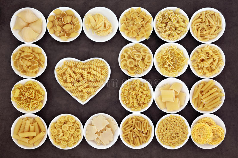 I Love Pasta. Large pasta food selection in round bowls and in a heart shaped bowl over brown background royalty free stock photos