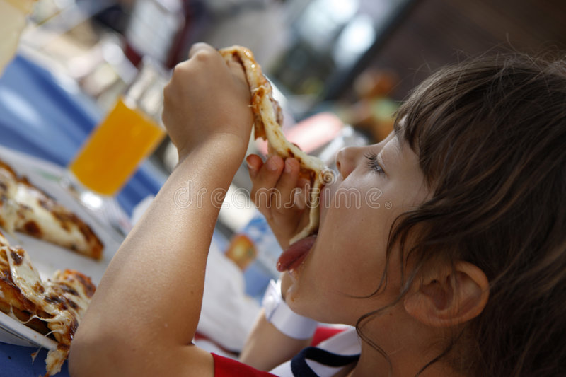 I love pizza. Young girl is eating pizza stock images