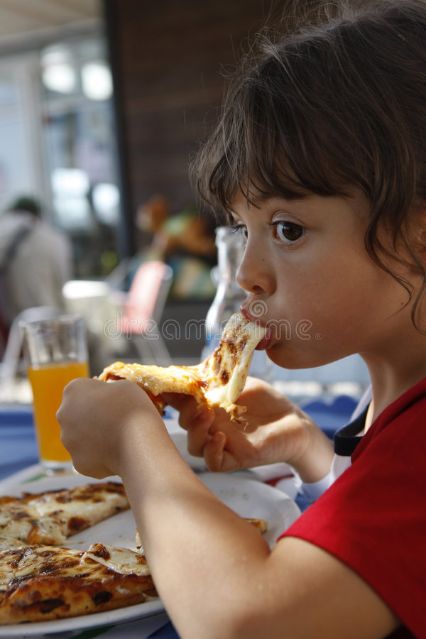 I love pizza. Young girl is eating pizza stock photography