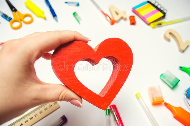 I Love School! the student holds the heart in his hands on the background of the desk. love of learning. school supplies. statione royalty free stock images