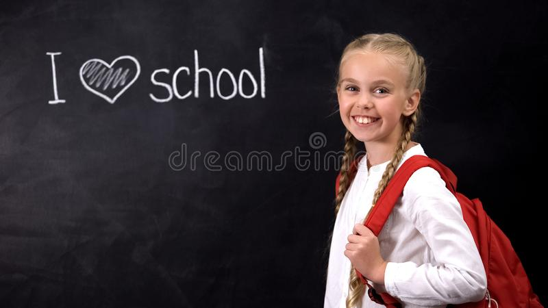I love school written on blackboard, cute girl standing near, primary education stock images