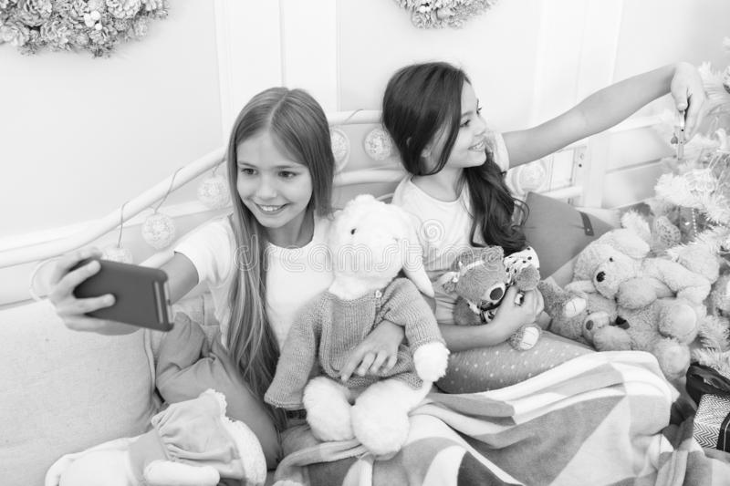 I love selfie. Taking Christmas and New Year selfie with smartphone. Little girls use phone in bed. Happy little royalty free stock photo