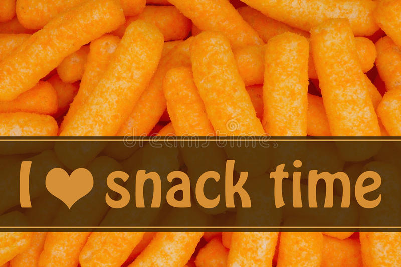 I love snack time message. Orange cheese puff snack background with text I heart snack time royalty free stock photography