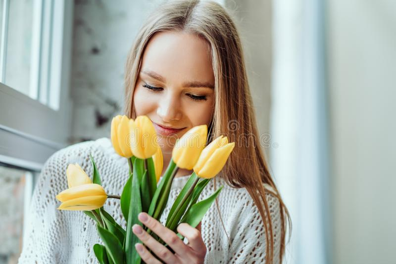 I love spring and flowers. Portrait of beautiful woman with bouquet of yellow tulips. Beauty and tenderness concept stock photos