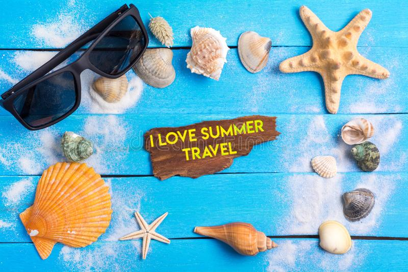 I love summer travel text with summer settings concept. I love summer travel text On Beach Accessories With Few Marine Items On Blue Wooden Plank , Summer royalty free stock photography