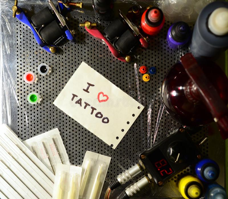 I love tattoo. The text is written on a small sheet of paper among various equipment for tattooing royalty free stock image