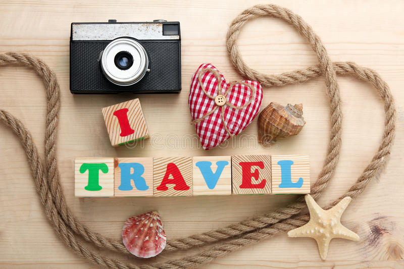 I love travel. The camera and the rope with seashells on a wooden brown background and wooden cubes with the words `I love travel royalty free stock images