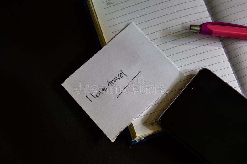 I love travel word written on paper. I love travel text on workbook, Black background concept stock photography
