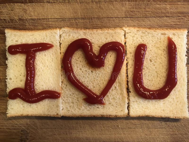 I Love U by bread on the wooden cutting board royalty free stock photos
