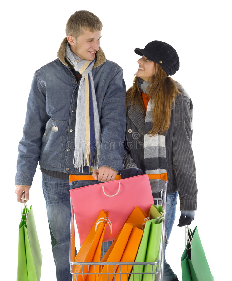 I love you... Young couple with full trolley. Smiling and looking at each other. White background, front view royalty free stock images