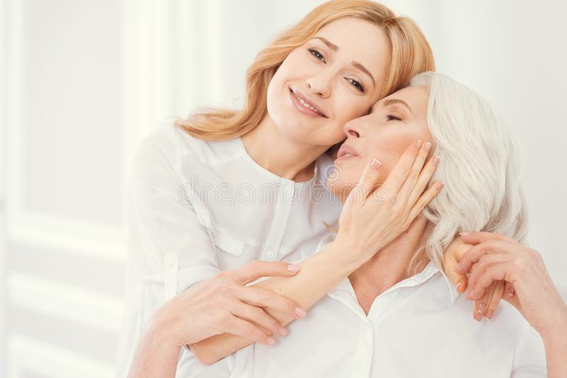 Tender adult daughter embracing her mother with love stock photography