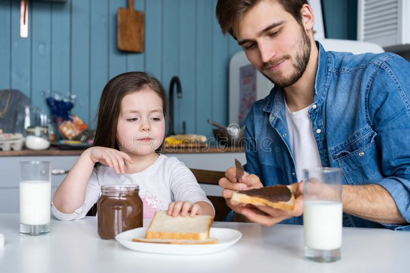 I love you, dad! Handsome young man at home with his little cute girl are having breakfast. I love you, dad! Handsome young men at home with his little cute royalty free stock photo
