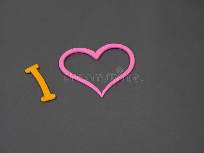 I love you inscription from plasticine with pink heart. On grey background royalty free stock photography