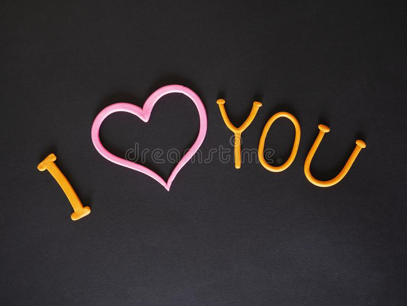 I love you inscription from plasticine with pink heart. On grey background stock photography